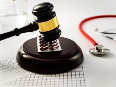 Judge gavel on tablets and pills, sentences a scam from the medical industry. Isolated on a white background.