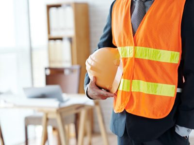 Cropped image of engineer with hardhat standing in office